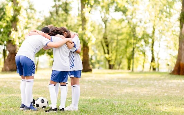 Kinderen moedigen elkaar aan voor een voetbalwedstrijd met kopie ruimte