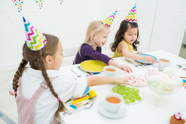 Kinderen nemen snoepjes van tafel op verjaardagsfeestje