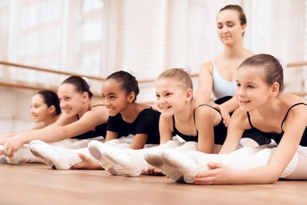 Kinderen oefenen stretch zitten en buigen.