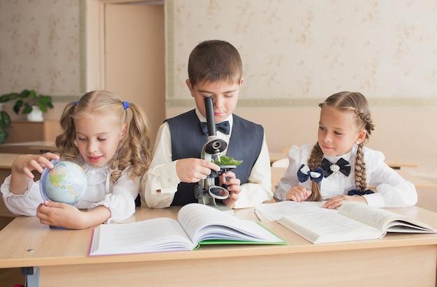 Kinderen of studenten met een microscoop studeren biologie in het schoollaboratorium