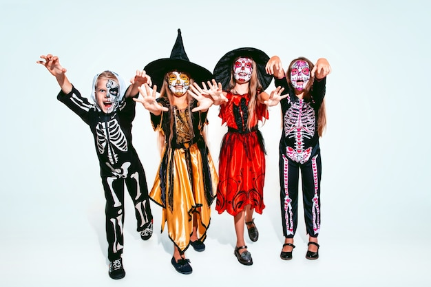 Kinderen of tieners houden van heksen en vampieren met botten en glitter op blanke modellen als achtergrond