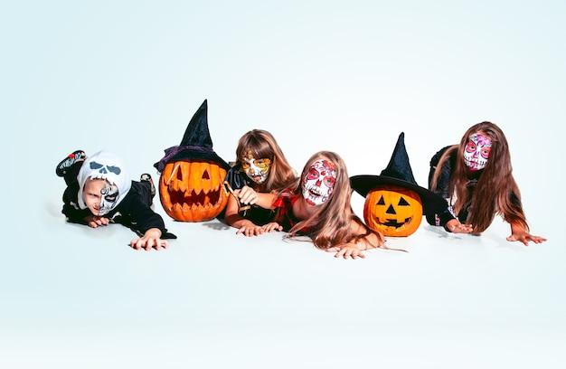 Kinderen of tieners houden van heksen en vampieren met botten en pompoen op blanke modellen als achtergrond