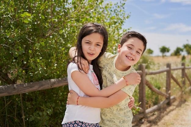Kinderen omhelsden vrolijk lachend in een park met een houten hek erachter