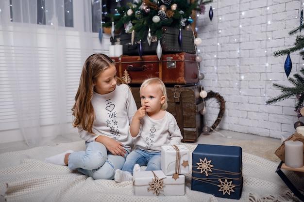 Kinderen onder de kerstboom met geschenkdozen. nieuwjaars versieringen. rustieke stijl, donkere houten decoraties nieuwjaarsinterieur. zusters.