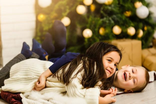 Kinderen onder de kerstboom met geschenkdozen
