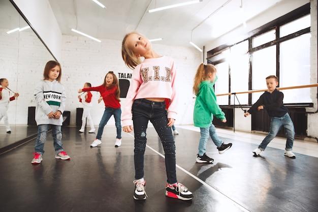Kinderen op dansschool. ballet, hiphop, straat, funky en moderne dansers over studioachtergrond.
