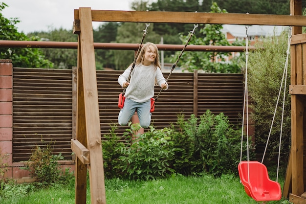 Kinderen op de schommel. meisje swingende op een schommel in de tuin. zomerplezier.