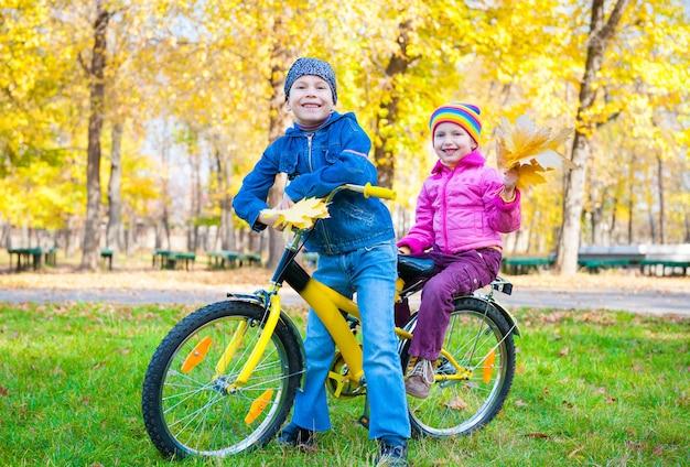 Kinderen op een fiets in de herfstpark