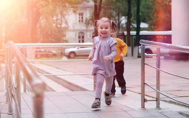 Kinderen op een wandeling in het voorjaar in het stadspark. het meisje loopt in het park. kinderen en moeder lopen door de stad.