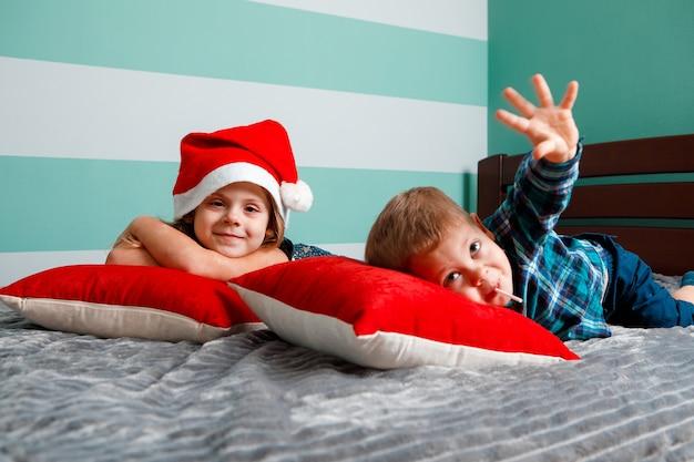 Kinderen op het bed zijn gekleed voor het nieuwe jaar