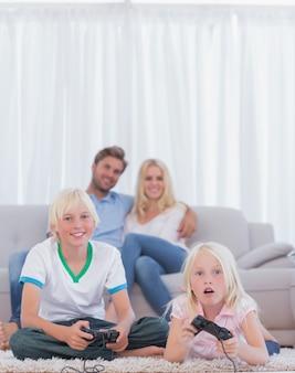 Kinderen op het tapijt spelen videogames terwijl hun ouders naar ze kijken