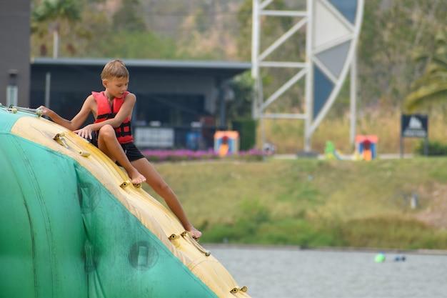 Kinderen op opblaasbare attracties in het water.