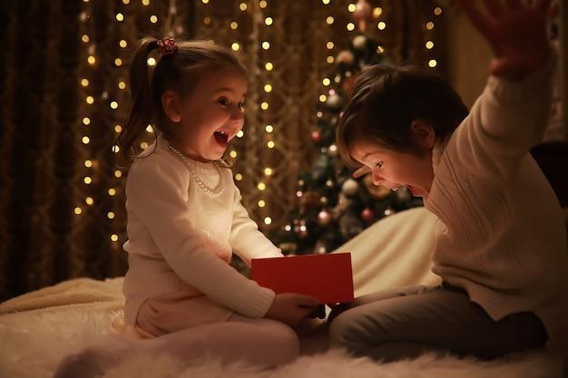 Kinderen openen kerstcadeautjes kinderen onder de kerstboom met geschenkdozen