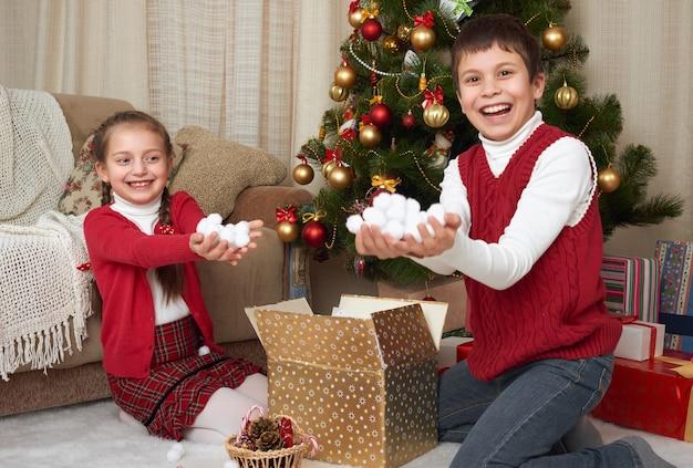 Kinderen pakken geschenkdozen uit in de buurt van de kerstboom en laten een handvol sneeuw zien