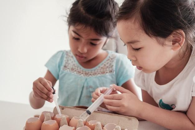 Kinderen planten zaailingen in hergebruik eierschalen, montessori homeschool onderwijs