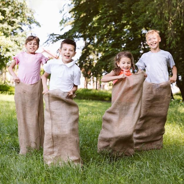 Kinderen plezier spelen met jute zakken