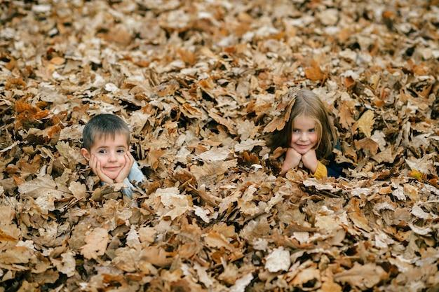 Kinderen poseren in de herfstbladeren