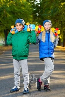 Kinderen poseren met skateboard buitenshuis