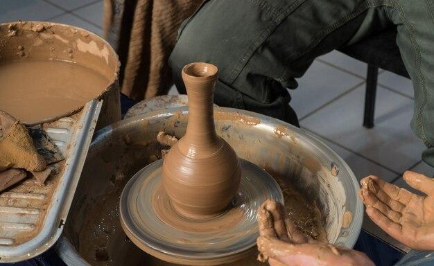 Kinderen pottenbakken leren. de docent geeft een masterclass in modelleren