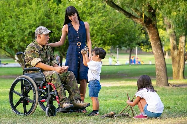 Kinderen regelen hout voor kampvuur in park in de buurt van moeder en gehandicapte militaire vader in rolstoel. jongen die logboek toont aan opgewekte vader. gehandicapte veteraan of familie buitenshuis concept