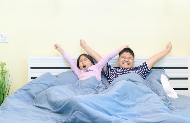 Kinderen rekken zich uit in bed na het wakker worden,