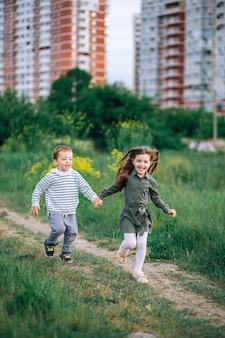 Kinderen rennen hand in hand over het pad de stad uit, ontsnappen aan de drukte van de stad.