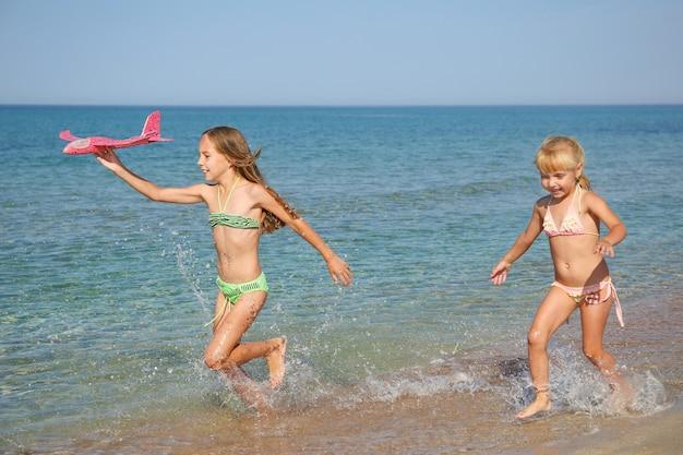 Kinderen rennen langs het strand.