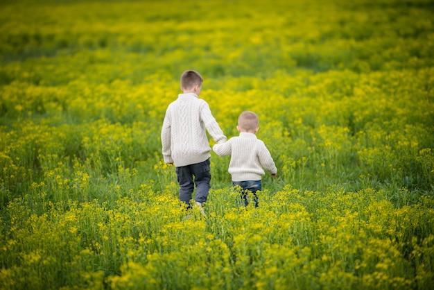 Kinderen rennen op het veld en hand in hand.
