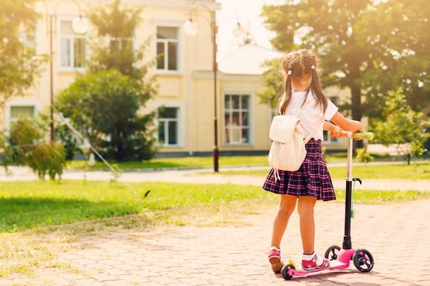 Kinderen rijden op scooters op weg naar school