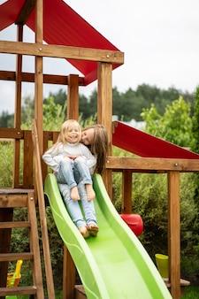 Kinderen rijden van de glijbaan, zussen spelen samen in de tuin