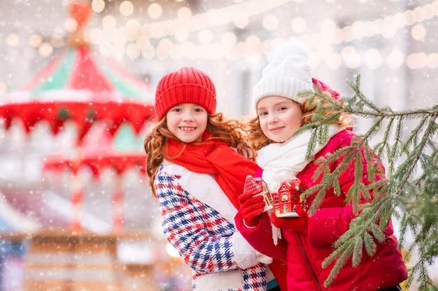 Kinderen, roodharige zussen, verschuilen zich achter een boom met speelgoed in hun handen op de feestelijk versierde kerstmarkt in de stad.