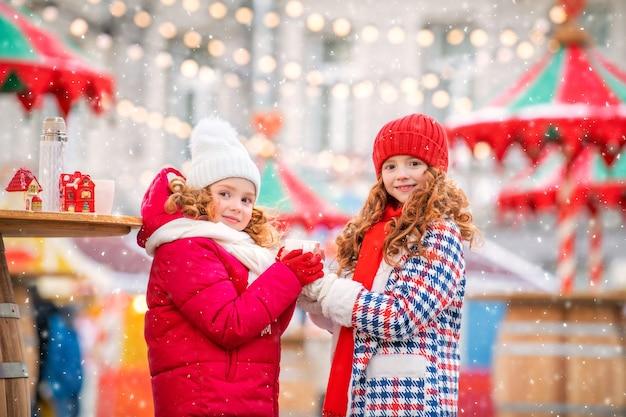 Kinderen, roodharige zussen verwarmen hun gehandschoende handen met een mok hete thee op een feestelijk versierde kerstmarkt in de stad.