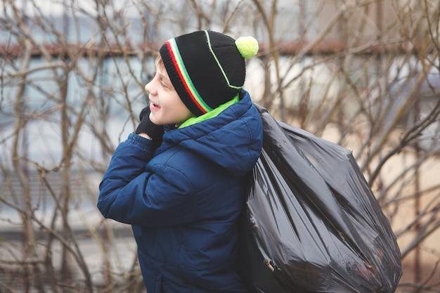 Kinderen ruimen afval op op het schoolplein. het concept van milieubescherming. schooljongens dragen zwarte vuilniszakken.