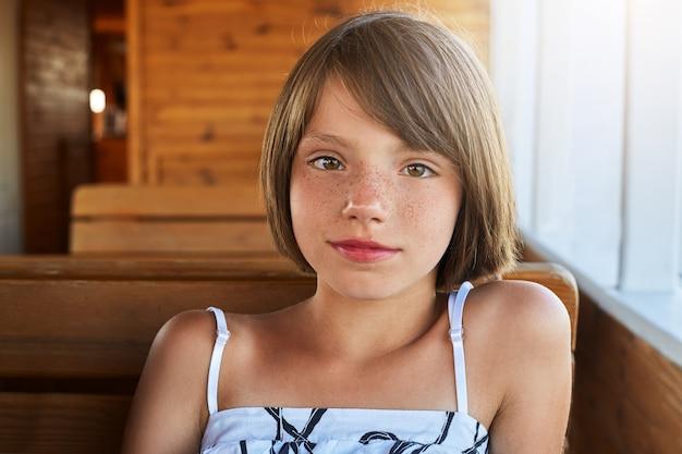 Kinderen, rust, ontspanning concept. aangenaam ogend meisje met sproeten met kort donker haar, gekleed in zomerjurk zittend op het dek op een houten bankje, met haar glanzende ogen recht in de camera kijkend