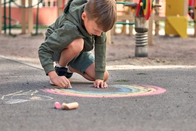 Kinderen schilderen buiten. portret van een kindjongen die een regenboogkleurig krijt trekt op het asfalt op een zonnige zomerdag. kinderen spelen op de speelplaats. buiten activiteit