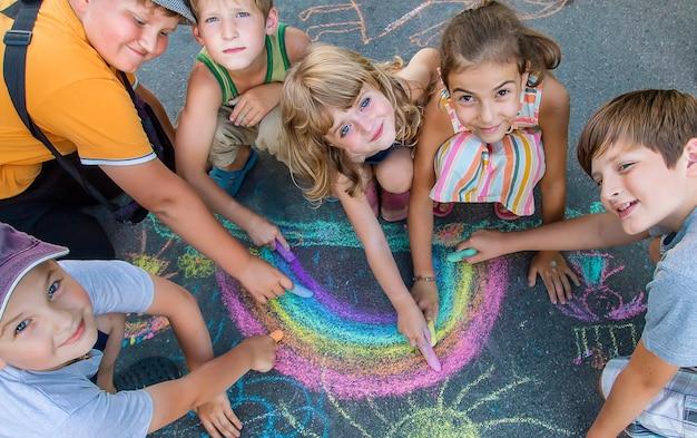 Kinderen schilderen een regenboog op het asfalt. selectieve aandacht. kinderen.