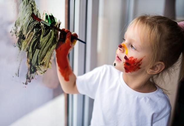 Kinderen schilderen een regenboog op het raam
