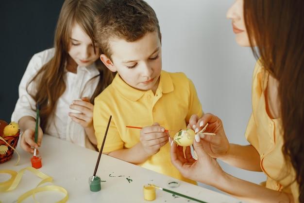 Kinderen schilderen eieren. moeder leert kinderen. zittend aan een witte tafel.