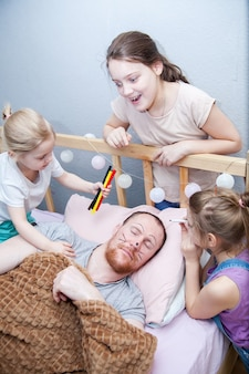 Kinderen schilderen het gezicht van hun vader terwijl hij slaapt op 1 april
