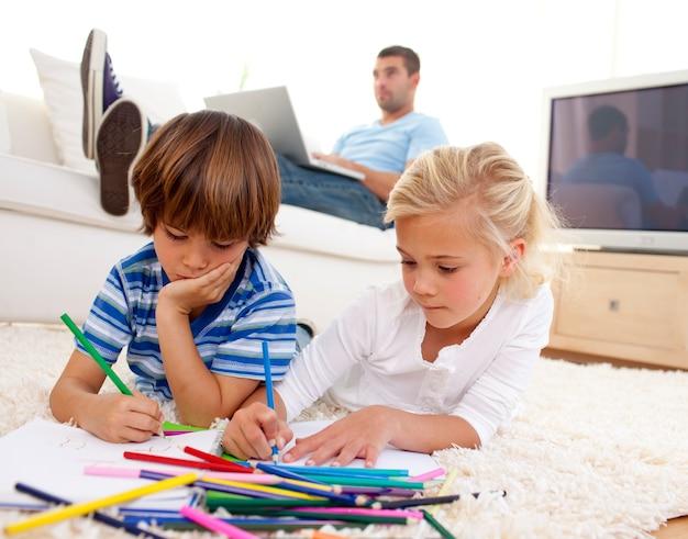 Kinderen schilderen in de woonkamer en vader met een laptop