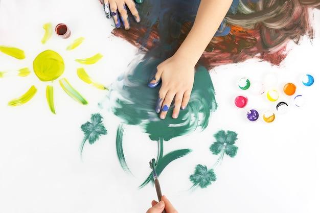 Kinderen schilderen met de hand een foto met verf op een wit oppervlak