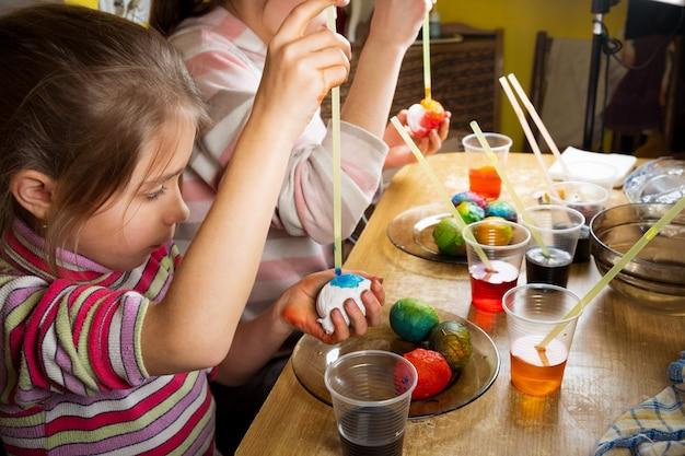 Kinderen schilderen op ongebruikelijke wijze paaseieren met kleurrijke kleurstoffen