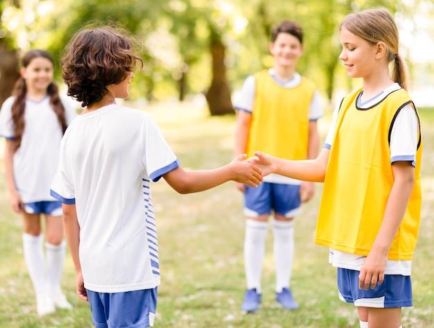 Kinderen schudden elkaar de hand voor een voetbalwedstrijd