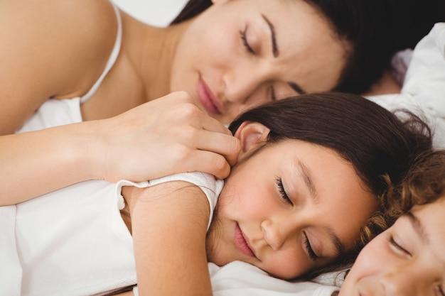 Kinderen slapen met moeder op bed
