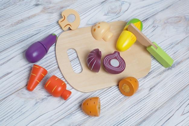 Kinderen speelgoed houten groenten. kinderen ontwikkelen houten spel. een set van houten groenten met ruimte voor tekst. plastic speelgoedkeuken voor kinderen. gesneden speelgoedgroenten