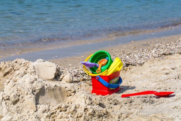 Kinderen speelgoed op zandstrand tegen de zee