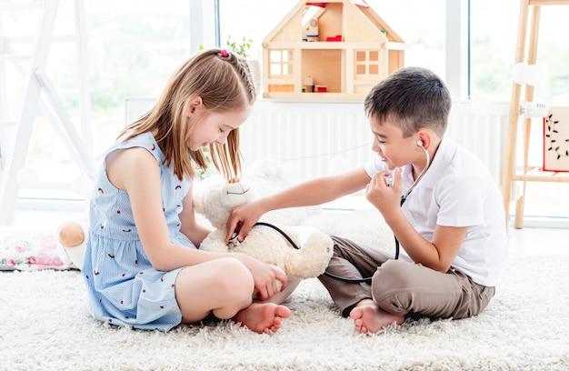 Kinderen spelen arts met teddybeer