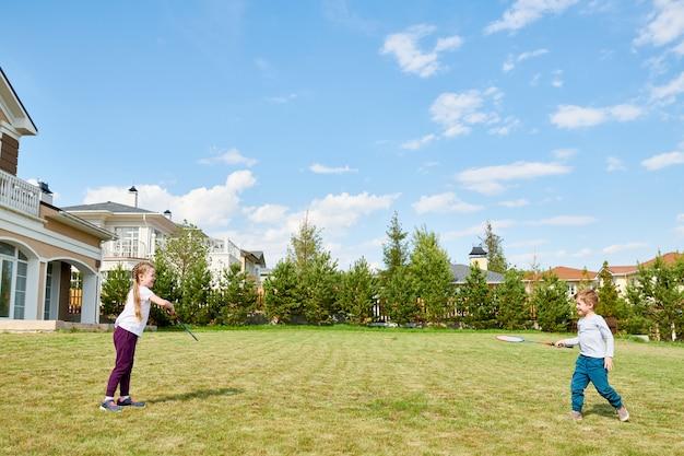 Kinderen spelen badminton in voortuin