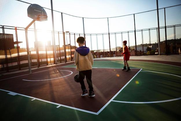 Kinderen spelen basketbal op een veld