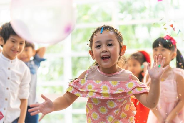Kinderen spelen en gooien papier in een kinderfeestje